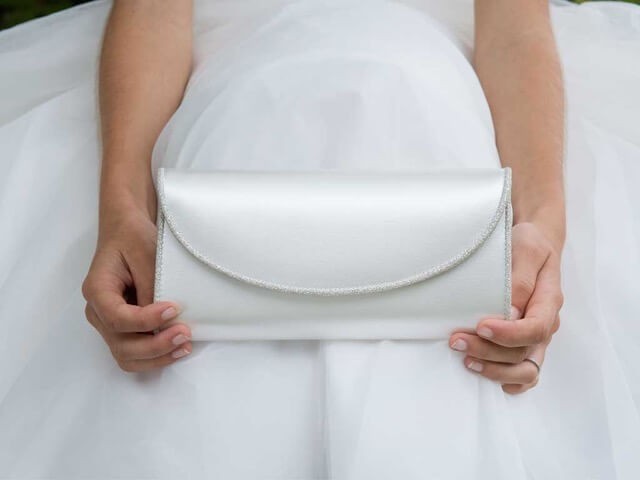 Rainbow Club Viki clutch bag. The bag is crafted from a blend of ivory satin and silver fine shimmer and is a rectangular shape with a curved fold over front piped with exclusive Italian silver fine shimmer