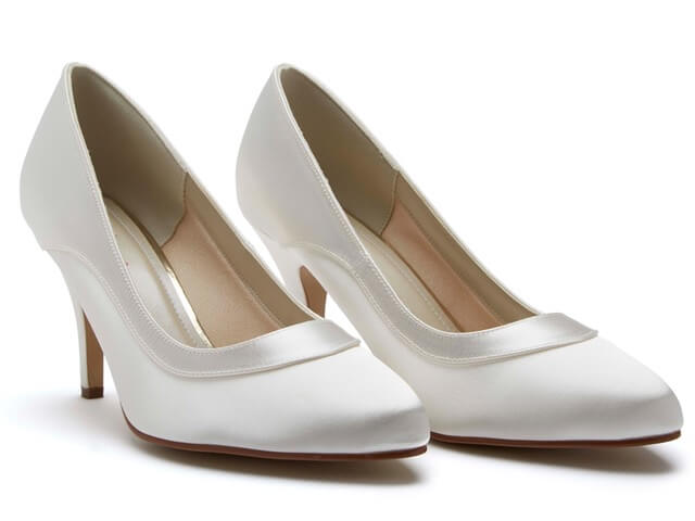 Rainbow Club Nicole ivory satin bridal shoes. They feature a chic almond toe, slender, mid-height heel and are finished with a statement satin overlay trim