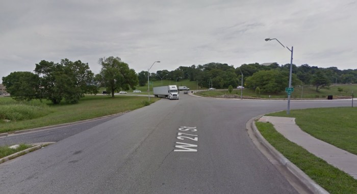 This sidewalk directs pedestrians directly into a highway on-ramp on the way to some distant refuge.