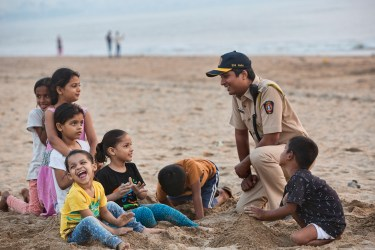 Policeman with kids on the beach