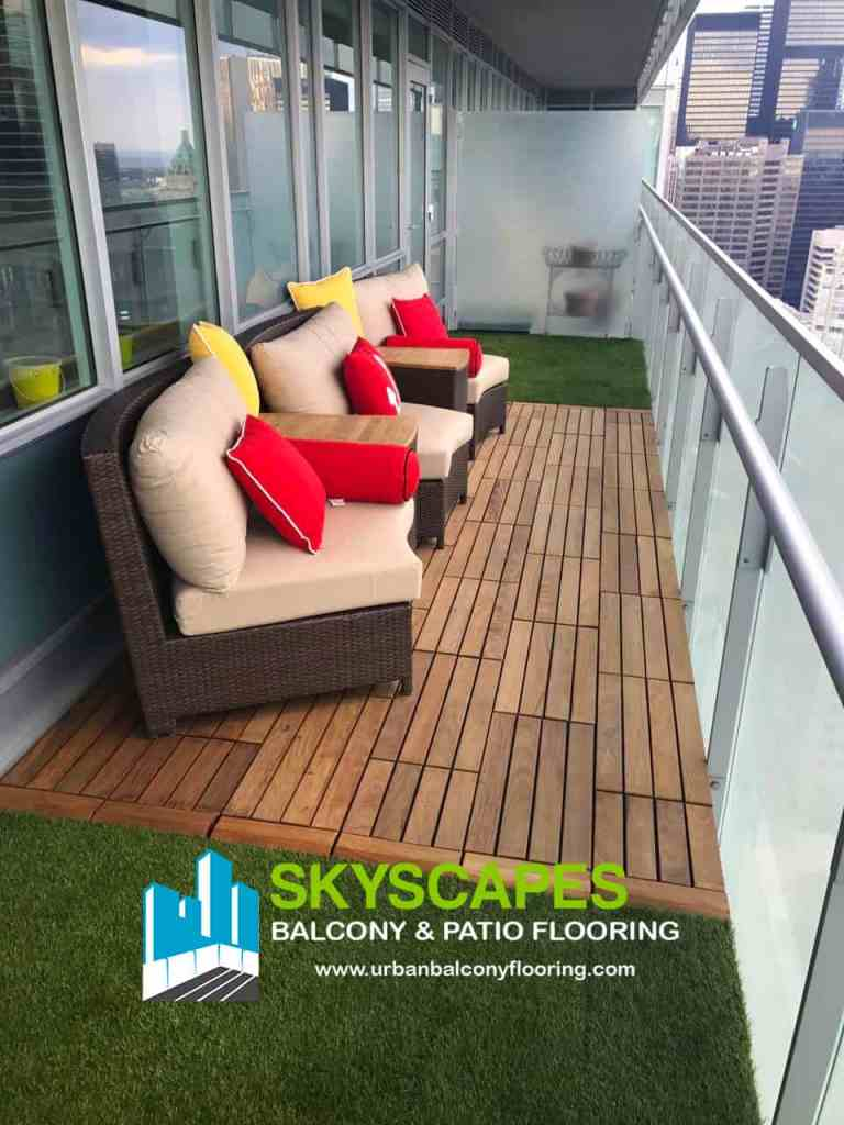 Staggered Ipe wood tiles in an island of synthetic, interlocking grass tiles. Skyscapes green and blue logo at bottom of image.