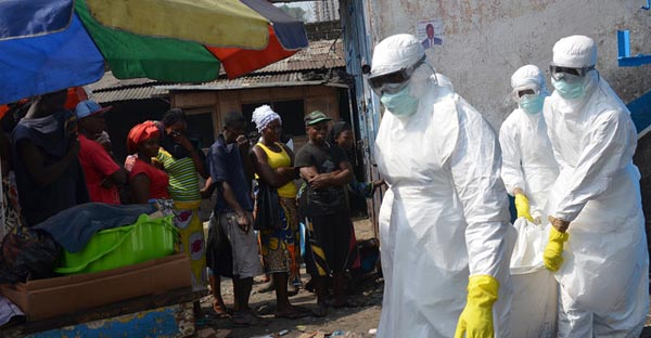 Red cross workers, wearing protective suits, carry the body of a person who died from Ebola during a burial with relatives of the victims of the virus, in Monrovia. (Zoom Dosso/AFP via Getty Images)