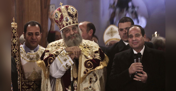 Egypt's President Abdel-Fattah El-Sisi, right, visits Coptic Pope Tawadros II, center, during Christmas Eve Mass at St. Mark's Cathedral, in Cairo, Egypt, Tuesday, Jan. 6, 2015 (AP)