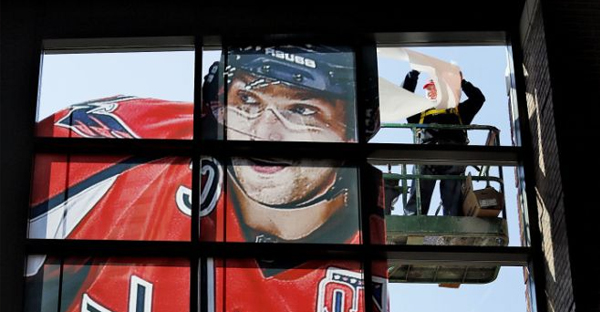 Josh Gallant, a worker for CGS Imaging, installs a giant image of Alexander Ovechkin of the Washington Capitals, one of the All-Stars due in Columbus for Sunday's game, on the windows on the west side of Nationwide Arena. (CHRIS RUSSELL | DISPATCH)