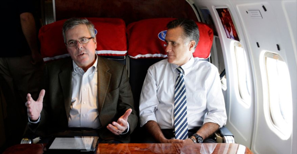 Republican presidential candidate Mitt Romney (right) talks with former Florida Gov. Jeb Bush as they fly on Mr. Romney's campaign plane to Miami on Wednesday, Oct. 31, 2012. (AP Photo/Charles Dharapak)