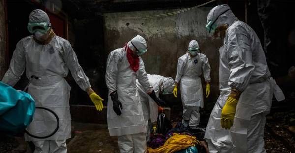 Members of a Liberian Red Cross burial team, under contract from the Liberian Ministry of Health, remove the body of suspected Ebola victim Lorpu David, 30, on Sept. 18, 2014, in the Gurley street community in central Monrovia, Liberia. (DANIEL BEREHULAK—THE NEW YORK TIMES/REDUX)