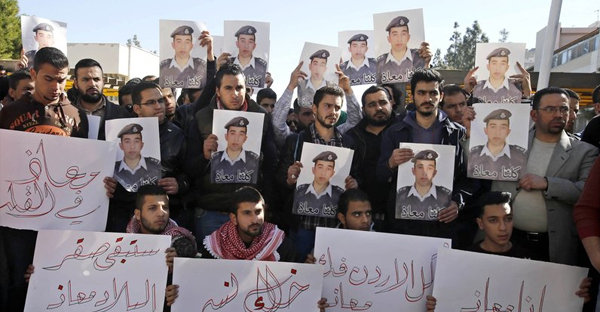 """Supporters of Jordanian pilot Lt. Muath al-Kaseasbeh hold posters of him that read, """"We are all Muath,"""" during a protest in Amman, Jordan, on Tuesday. (Raad Adayleh/AP)"""