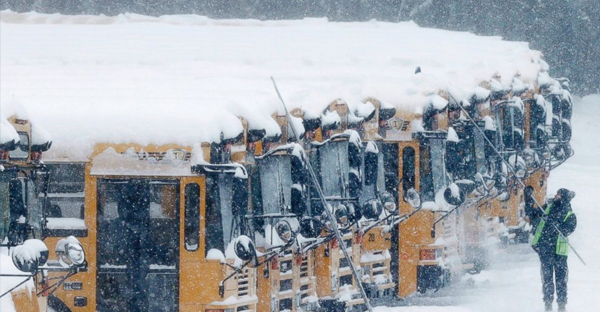 A driver cleans snow off school buses in Derry, N.H., Feb. 2, 2015. (Charles Krupa/AP Photo)