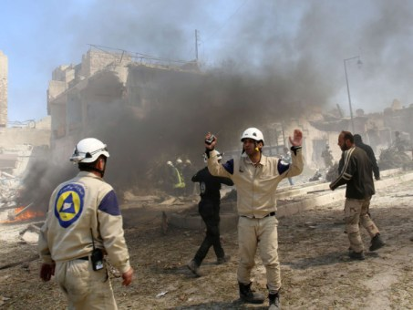 Syrian rescue workers and firefighters work next to a burning building following reported air strikes by government forces on a rebel held area in the northern Syrian city of Aleppo on April 17, 2015. The conflict in Syria has left more than 220,000 dead since it began four years ago with an uprising against President Bashar al-Assad, a key monitoring group said on April 16, 2015.    AFP PHOTO / AMC / FADI AL-HALABIFadi al-Halabi/AFP/Getty Images