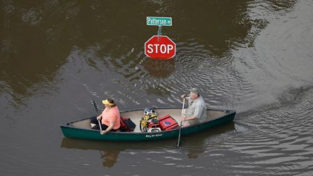 In this aerial photo, people canoe through floodwaters past a stop sign near Bear Creek Park Saturday, May 30, 2015, in Houston. David J. Phillip/AP Photo