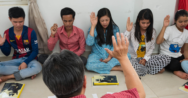 Ben Lin,* a Southern Baptist worker, asks Southeast Asian students to raise their hand if they want to trust in Jesus. The students were challenged to leave Buddhism completely. For many, coming from a Buddhist background, total commitment to a one, true God isn't an easy concept to grasp. (Photo by Luke In/IMB)