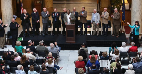 Rev. Carl Kelley, associate minister at Phillips Temple CME in Indianapolis, at podium, is flanked by pastors standing on a stage in the north atrium of the Indiana Statehouse on Monday, April 27, 2015 during the Indiana Pastors Alliance rally opposing changes Indiana lawmakers made to the Religious Freedom Restoration Act that Gov. Mike Pence signed earlier this month.  (Charlie Nye / The Star)