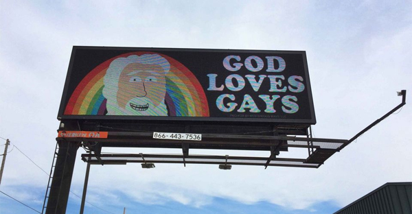A billboard stating 'God Loves Gays' went up on Telegraph Road in Dearborn Heights recently. The billboard with a caricature of God is one of several rotating on the electronic billboard. (Photo by Ian Thibodeau)