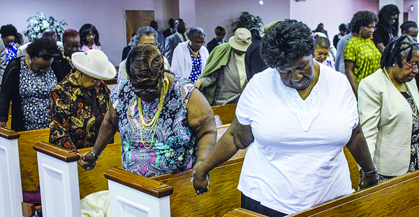 Members of the Central Church of Christ in Baltimore hold hands as they stand and pray during a Sunday morning worship assembly. (PHOTO BY BOBBY ROSS JR.)