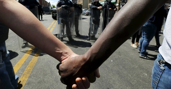 Members of the community hold hands in front of police officers in riot gear outside a recently looted and burned CVS store in Baltimore on April 28. (Reuters /Jim Bourg)