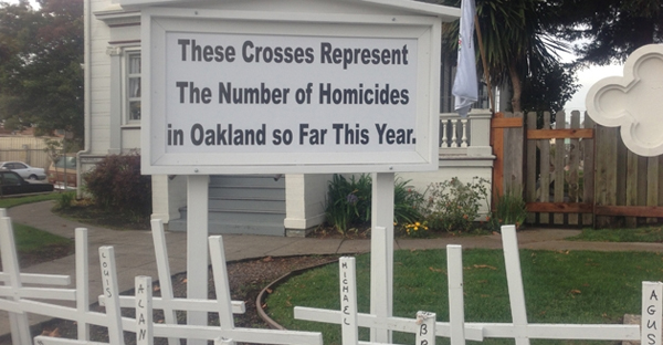 The sign in front of the St. Columba Parish rectory explains the crosses erected for every Oakland, Calif., homicide victim during a given year. (Courtesy of Rich Laufenberg)