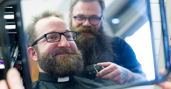 Vicar Adam Atkinson getting a beard trim from barber Steve Murphy, at Hound Dog Barbers in Hackney (Photo: Eddie Mulholland)