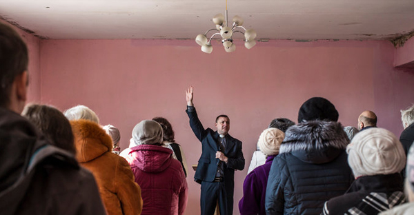 Sergei N. Kosyak led a service at the Christian Aid Center of the Transfiguration Church in Maryinka, Ukraine, last month. (Credit: Brendan Hoffman for The New York Times)