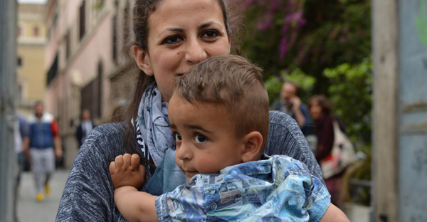The youngest Syrian refugee aboard the papal plane was 2-year-old Riyad, carried here by his mother Nour. (Religion News Service photo by Rosie Scammell)