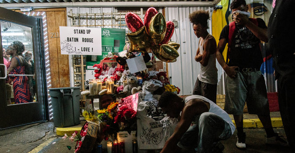 Mourners placed candles and flowers in the parking lot of the Triple S Food Mart on Wednesday. (Credit: William Widmer for The New York Times)