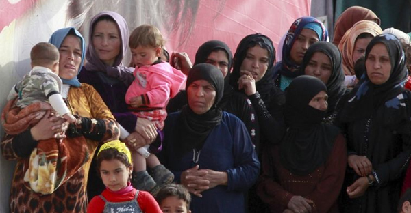 Syrian refugees stand outside tents during the visit of United Nations Secretary-General Ban Ki-Moon to al-Dalhamiyeh camp in the Bekaa Valley, Lebanon on March 25, 2016. (Reuters)