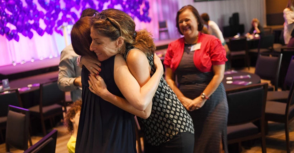 Joyce Gottesfeld, MD, center, hugs Cassidy Smith during a Bonfils Blood Center banquet at Seawell Ballroom in Denver Performing Arts Complex, August 18, 2016. Gottesfeld delivered Cassidy's daughter, at Denver's St. Joseph Hospital in 2012, and help save her life. (RJ Sangosti, The Denver Post)
