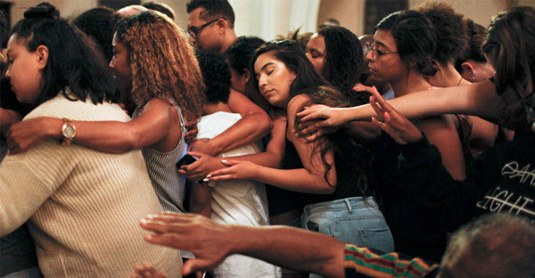 The McCarty Memorial Christian Church congregation comes together to embrace a man who recently lost his brother at the hands of police. (Harrison Hill / Los Angeles Times)