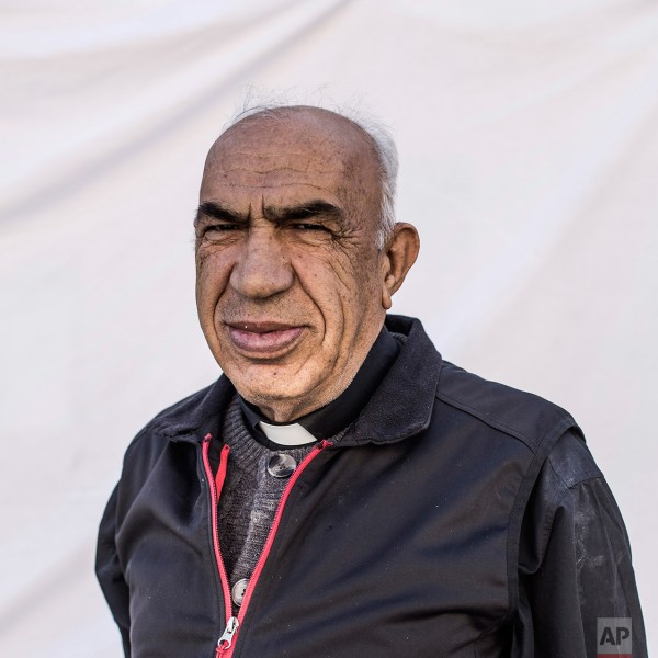 Father Khouri Youssef, 72, a spiritual leader of the community, poses for a portrait in the Karamlis complex, where Christians displaced by Islamic State militants are living, in Irbil, Iraq, Friday, Dec. 23, 2016. Iraq's Christians are marking the holiday in his camp for displaced people with a sense of worry and despair, unable to return to their towns they were forced to flee two years ago by the Islamic State group's onslaught. (AP Photo/Manu Brabo)