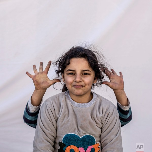 Mariam Saad, 7, and a friend play while posing for a portrait in the Karamlis complex, where Christians displaced by Islamic State militants are living, in Irbil, Iraq, Friday, Dec. 23, 2016. Iraq's Christians are marking the holiday in his camp for displaced people with a sense of worry and despair, unable to return to their towns they were forced to flee two years ago by the Islamic State group's onslaught. (AP Photo/Manu Brabo)