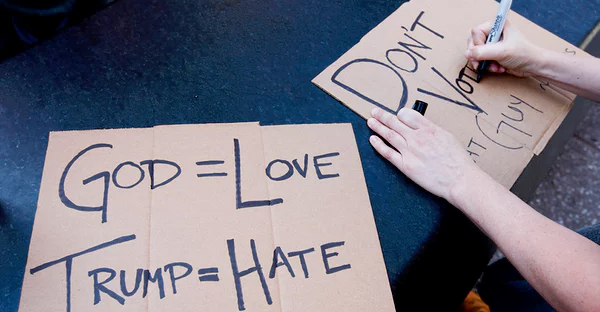 A woman writes out a sign before joining a demonstration representing multiple religious faiths against Donald Trump. (Photograph: Justin Lane/EPA)