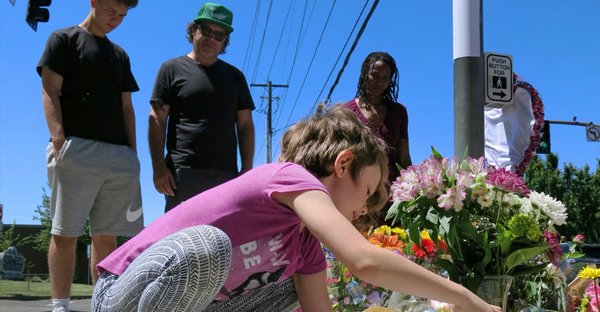 Coco Douglas, 8, on Saturday at a memorial in Portland, Ore., for two men who were killed when they confronted a man yelling anti-Muslim insults at two women on a commuter train. (Credit: Gillian Flaccus/Associated Press)