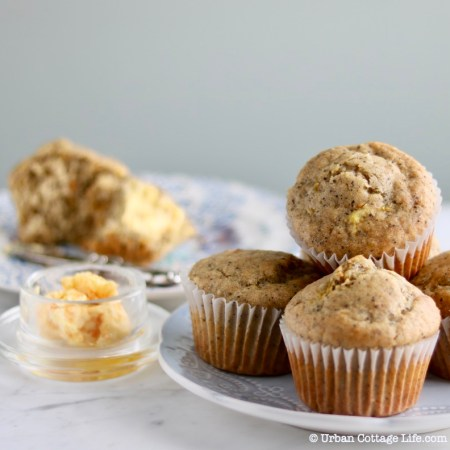 A plate of 4 orange poppyseed muffins with a plate with a partially eaten muffin spread with orange maple butter in the background.