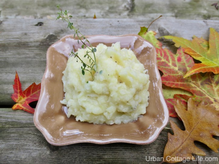 A dish of mashed potatoes garnished with a sprig of thyme on a bed of colourful maple and oak leaves