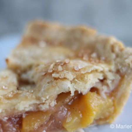 A close-up shot of a slice of peach pie, showing the flaky laters of the pastry