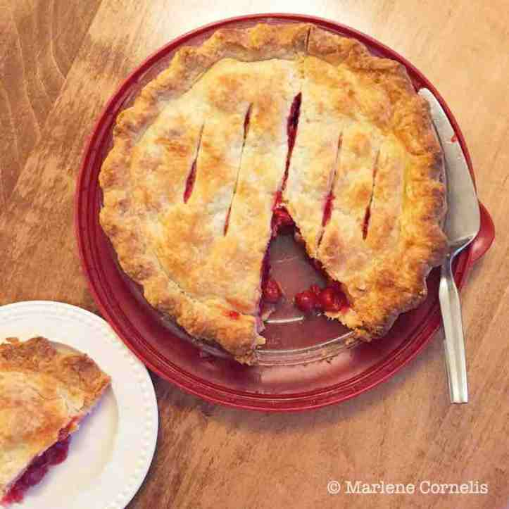 An overhead shot of a cherry pie with a slice cut on and sitting on a plate