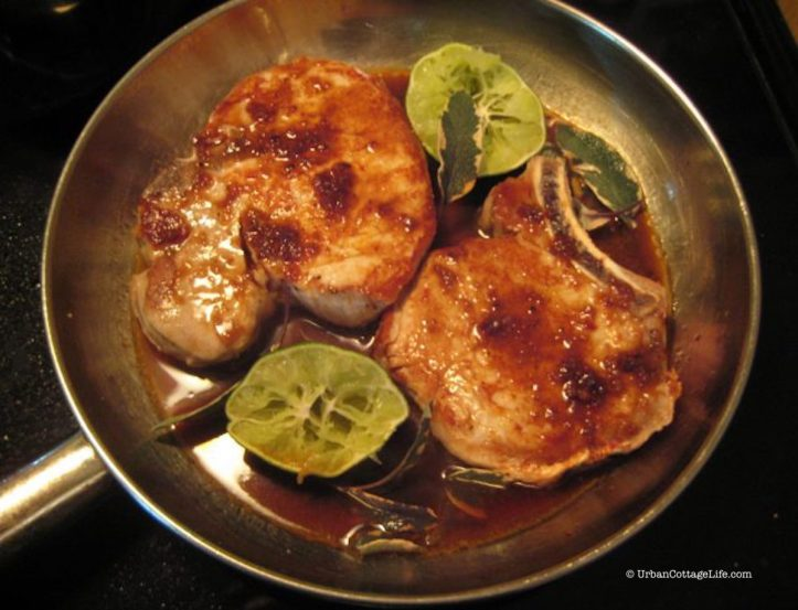 Seared pork chops with sauce, sage and squeezed limes, ready for roasting