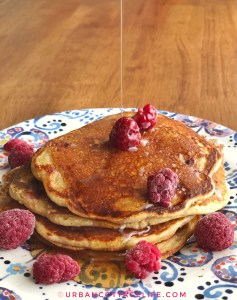 Maple syrup drizzles onto a stack of cornmeal raspberry pancakes strewn with raspberries
