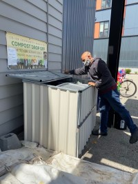 Man opening the compost bins to drop off kitchen scraps