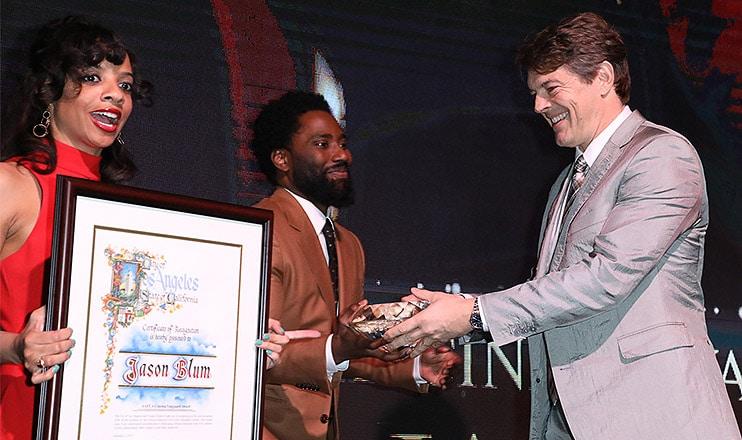 "Jason Blum receives the Cinema Vanguard Award from ""BlacKkKlansman"" star John David Washington at the 10th Annual AAFCA Awards. (Credit: ©2019 Sheri Determan)"
