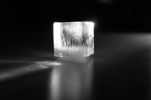 Reduce puffiness and dark circles by placing an ice cube on the roof of your mouth with your tongue. As the ice melts, the cold will penetrate eliminating puffiness and lightening underneath the eyes. Applying Preparation H over bags also helps.