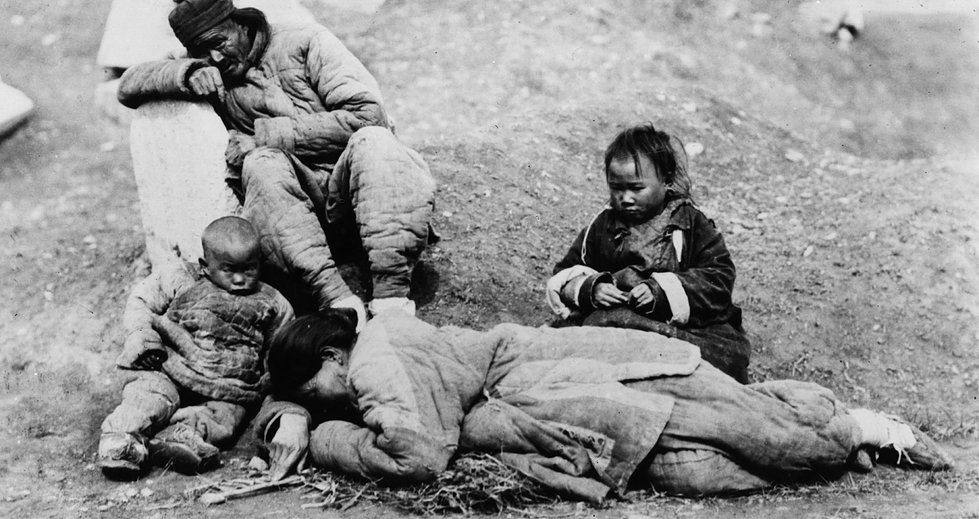 Typical famine victims in China. A man grieves while children look at dying mother. (Photo by Topical Press Agency/Getty Images)