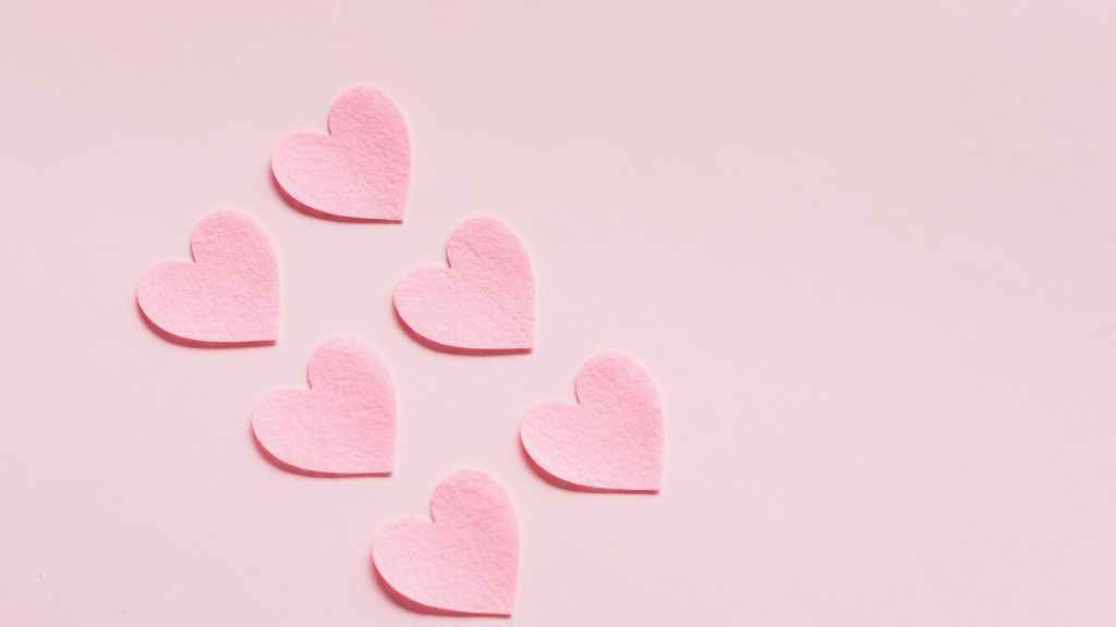 heart shaped papers on pink background