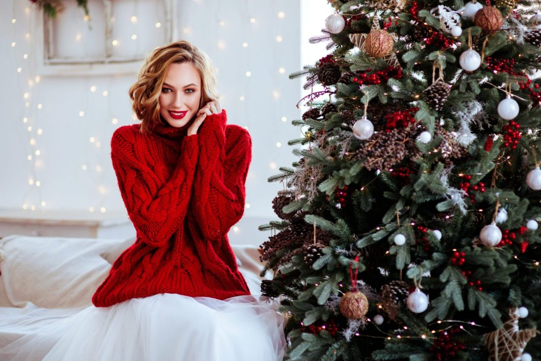 smiling woman in red sweater over christmas tree background