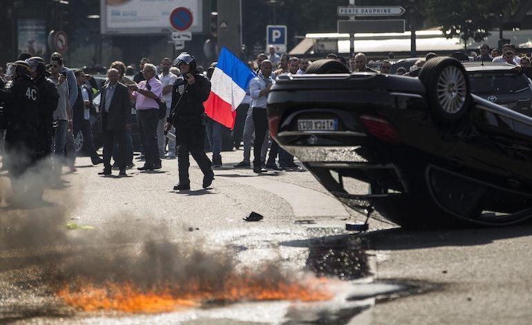 Кола на UberPOP беше преобърната от демонстрантите в Париж. ©EPA/БГНЕС