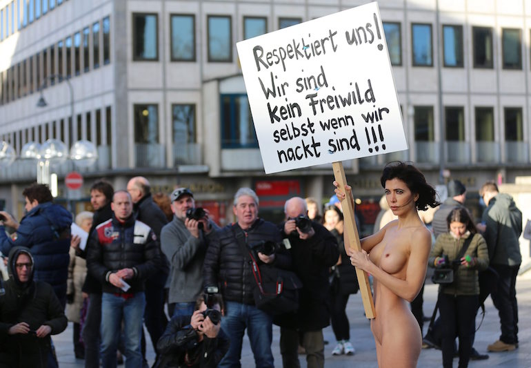 """Швейцарската артистка Мило Моар държи транспарант с надпис """"Уважавайте ни! Ние не сме беззащитна играчка, дори когато сме голи!"""" в знак на протест пред катедралата в Кьолн. ©EPA/БГНЕС"""
