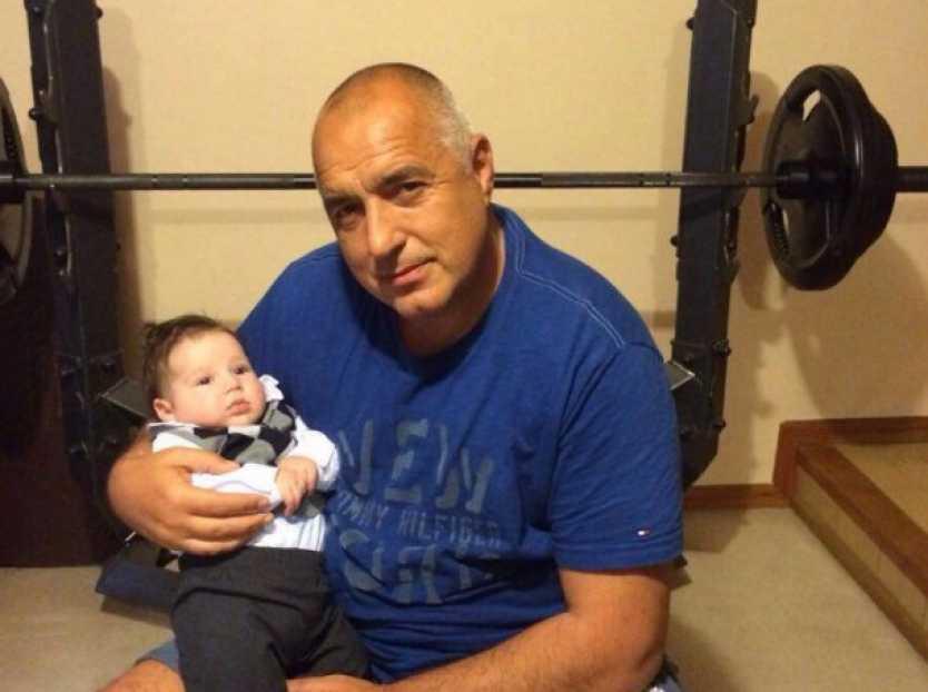 Бойко Борисов показва внука си на фона на лежанка във фитнес зала.
