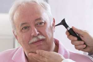Doctor checking elderly man's ear