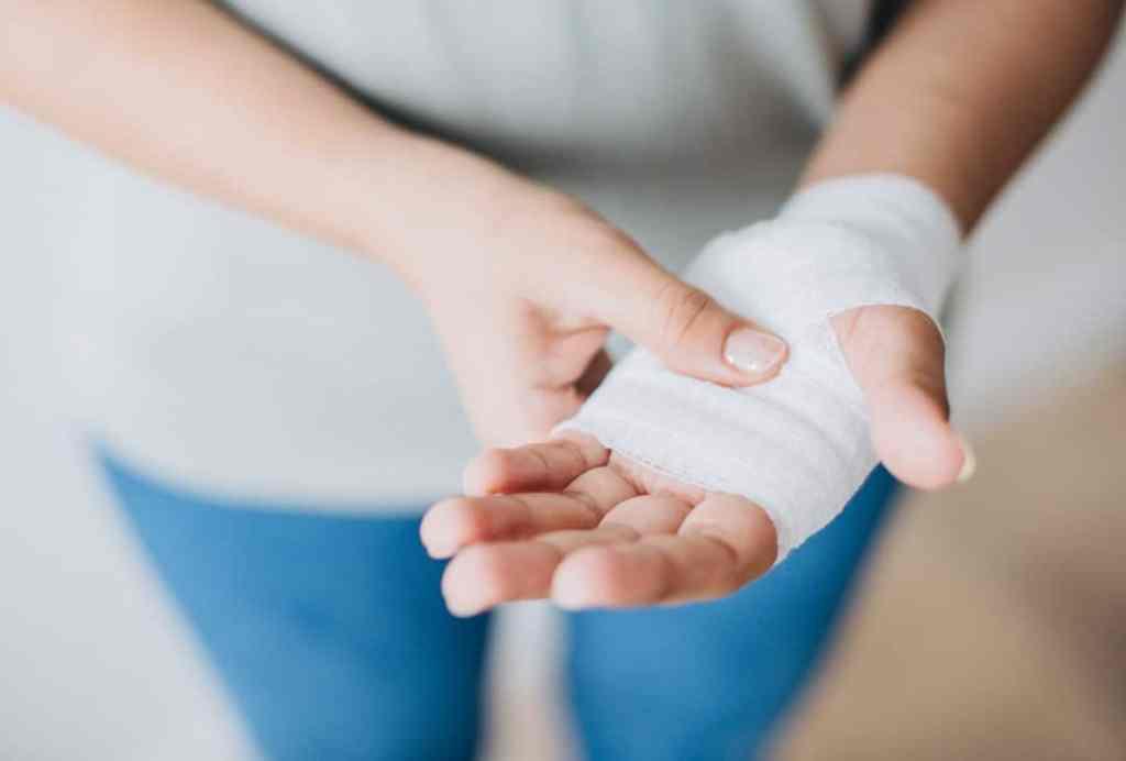 Woman holding bandaged-up hand