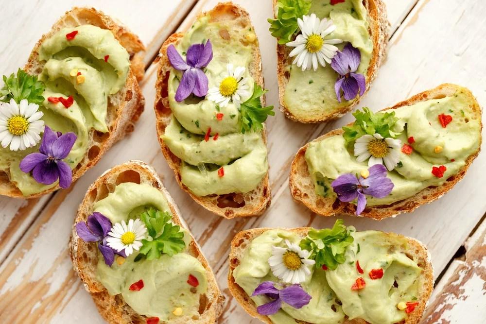 Brotschiffchen mit Avocado und Blumen. Auch bei Fleischverzicht kann der Vitamin B12 Bedarf gedeckt werden.