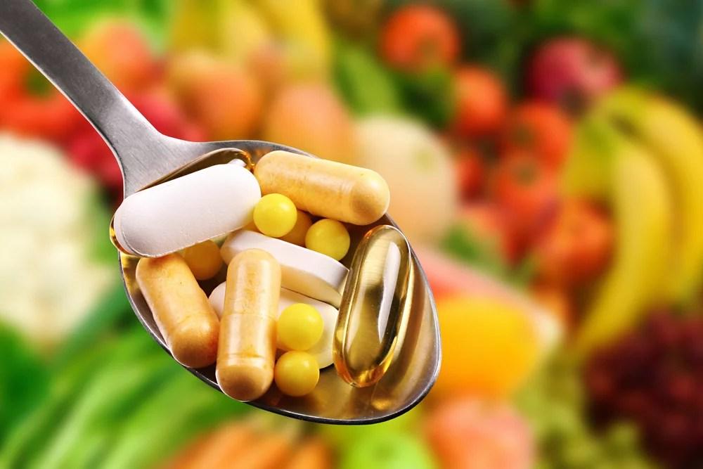 Löffel mit Nahrungsergänzungsmitteln. Vitamin B12: Hochdosiert färbt es den Urin rot.
